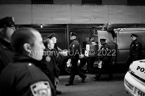 """New York, New York<br /> November 17, 2011<br /> <br /> """"Occupy Wall Street"""" protesters mark the movement's two-month milestone by marching from Zuccotti Park, in mass, to various access streets surrounding the New York Stock Exchange, which the police had barricaded off. Yet instead of the police keeping protesters out, protesters locked down those entrances to Wall Street and the New York Stock Exchange creating havoc as the police made more then 240 arrests to try and keep the streets open to normal traffic.<br /> <br /> While police and hundreds of protesters battle it out delivery men try to go on with business as usual."""