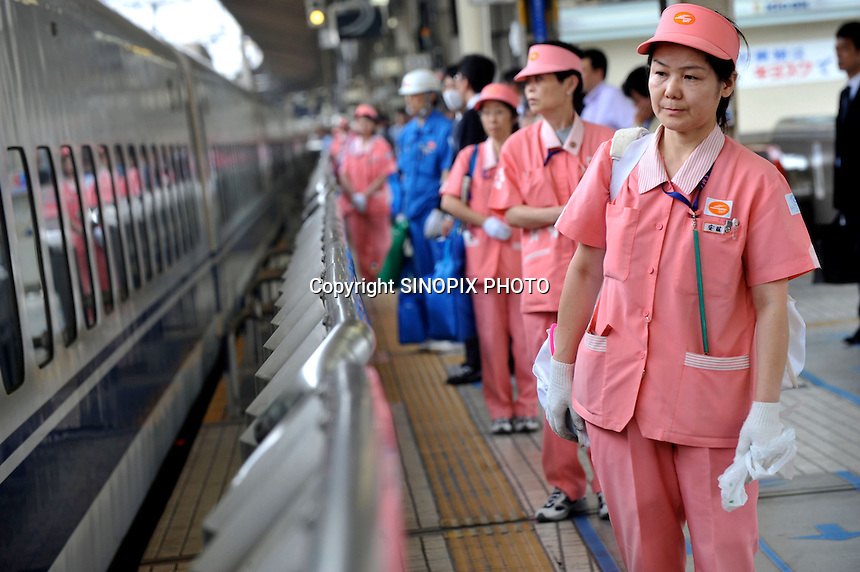 Japanese cleaning ladies line up to clean a Shinkansen  at Tokyo station Tokyo, Japan 4th June. <br /><br />Photo by Richard Jones/Sinopix