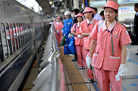 Japanese cleaning ladies line up to clean a Shinkansen  at Tokyo station Tokyo, Japan 4th June. <br />