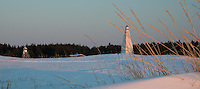 Keskiniemi lighthouse and beacon at sundown from the shoreline of Hailuoto Island -off Oulu Finland in the Gulf of Bothnia. Photo taken in early April.