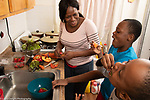 Mother in kitchen with 10 year old sons, food preparation, laughing as they eat fruit and lettuce, healthy snacks