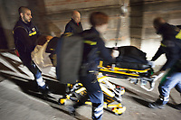 Switzerland. Canton Ticino. Sonvico. A woman lying down on an emergency medical stretcher is being transported from home. The woman is suffering from a stroke and needs to be brought urgently to the hospital for medical examinations. At night time on a narrow street, four paramedics are pushing the stretcher to the ambulance. The paramedics wear blue uniforms and work for theCroce Verde Lugano. The man (R) and the woman (center right) are professional certified nurses, the two others are volunteers specifically trained in emergency rescue. TheCroce Verde Lugano is a private organization which ensure health safety by addressing different emergencies services and rescue services. Volunteering is generally considered an altruistic activity where an individual provides services for no financial or social gain to benefit another person, group or organization. Volunteering is also renowned for skill development and is often intended to promote goodness or to improve human quality of life. 20.01.2018 © 2018 Didier Ruef