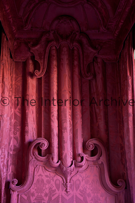 Detail of the vibrant pink bed hangings and carved headbord of a chinoiserie bed