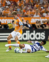 Houston Dynamo midfielder Stuart Holden (22) avoids the slide tackle by FC Dallas midfielder Marcelo Saragosa (5).  Houston Dynamo defeated FC Dallas 1-0 at Robertson Stadium in Houston, TX on May 9, 2009