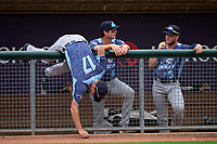West Michigan Whitecaps Parker Meadows (17) goes rock picking as Colt Keith (6) and Daniel Cabrera (5) look on during a weather delay before a game against the Lansing Lugnuts on August 24, 2021 at Jackson Field in Lansing, Michigan.  (Mike Janes/Four Seam Images)
