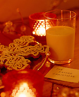 A biscuit and milk have been left for Santa beside a tealight on Christmas Eve