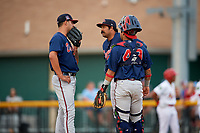 Danville Braves pitching coach Kanekoa Texeira (50) talks with starting pitcher Matt Rowland (27) and catcher Ricardo Rodriguez (49) in a mound visit during a game against the Johnson City Cardinals on July 28, 2018 at TVA Credit Union Ballpark in Johnson City, Tennessee.  Danville defeated Johnson City 7-4.  (Mike Janes/Four Seam Images)