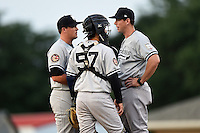 Staten Island Yankees pitching coach Tim Norton (47 - right) talks with pitcher Jonathan Holder (60 - left) as catcher Luis Torrens (57) listens in during a game against the Batavia Muckdogs on August 8, 2014 at Dwyer Stadium in Batavia, New York.  Staten Island defeated Batavia 4-2.  (Mike Janes/Four Seam Images)