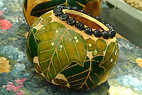 Hawaiian bowl or gourd with an intricate leaf design and kukui nuts at a craft fair on Lei Day.