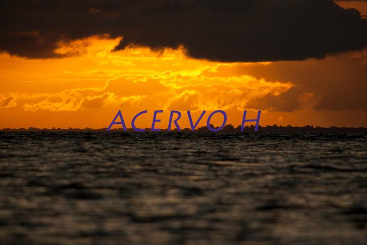 Pôr do sol na foz do Amazonas onde as águas do rio levam sedimentos ao mar criando grandes manguezais no litoral da região. A força das águas, aliada ao fenômeno da Pororoca na foz do Amazonas, causa o desmoronamento das margens  carregando consigo árvores, embarcações e outros objetos que se interponham à sua passagem violenta na região das ilhas Cavianas, um  dos últimos pedaços de terra no rio Amazonas em seu encontro com o  Atlântico.Marajó, Chaves, ilhas Caviana, Pará, Brasil.Foto: Paulo Santos17/06/2011