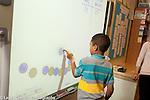 Education Elementary Grade 1 boy using digital white board math activity