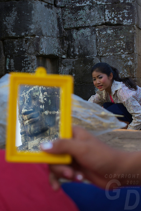 These local Khmer girls sometimes perform the Khmer ASARA dance for tourists at the Bayon temple, here they are at the end of the day taken of their make-up and I caught one of the faces from the bayon temple in the mirror.
