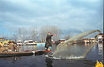 A Kashmiri fisherman throws his net in the waters of world famous Dal lake in kashmir valley. India