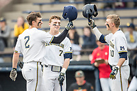 Michigan Wolverines outfielder Jonathan Engelmann (2) is greeted at the plate by teammates Jesse Franklin (7) and Blake Nelson (10) after hitting a home run against the Maryland Terrapins on April 13, 2018 in a Big Ten NCAA baseball game at Ray Fisher Stadium in Ann Arbor, Michigan. Michigan defeated Maryland 10-4. (Andrew Woolley/Four Seam Images)