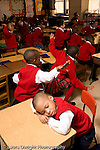K-8 Parochial School Bronx New York Kindergarten boy napping with head on desk while class does stretching or music activity vertical