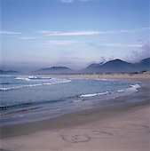 Florianopolis, Brazil. Praia da Joaquina surfer's beach with Atlantic Rainforest behind. Santa Catarina State.