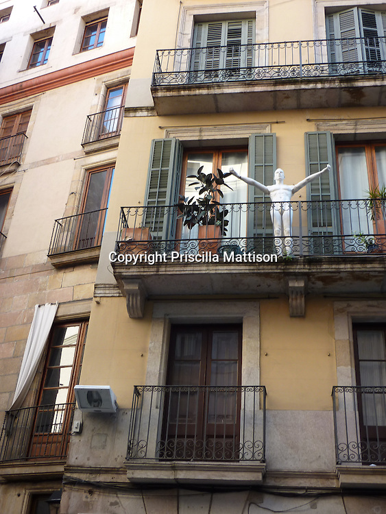 Barcelona, Spain - January 29, 2011:  A mannequin strikes a pose on an upper balcony.