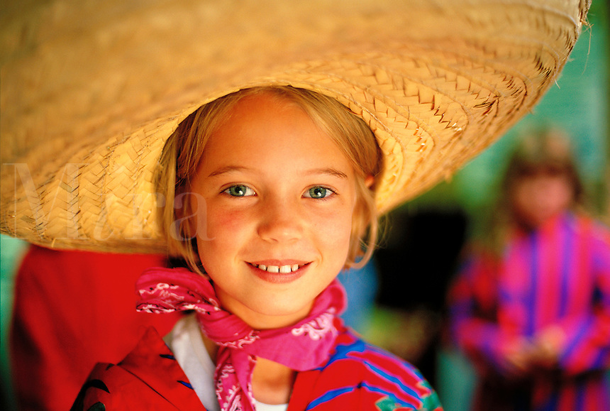Portrait of a smiling young girl wearing a straw sombrero hat and bandana.