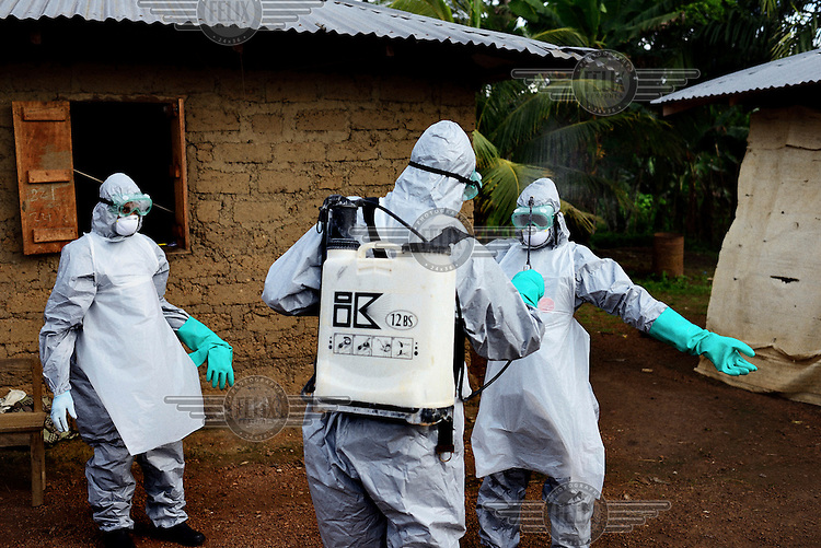 Members of the Red Cross spray themselves with chlorine after removing the body of Hauwa Ansmana (60) a suspected victim of Ebola, from her house in Gbeka village, inside the quarantine area. The government of Sierra Leone declared a state of emergency on 30 July and deployed troops to quarantine the hot spots of the epidemic. <br /> <br /> Sierra Leone is one of three countries severely affected by the Ebola outbreak in West Africa which started in Guinea in December 2013 and spread to neighbouring countries including Liberia, Senegal and Nigeria. By late September 2014 it had killed close to 3,000 people across the region, 554 in Sierra Leone alone, making it the worst outbreak of the disease since it was identified in 1976. It is believed that the reported number of cases and deaths may well exceed the official figures due to an unwillingness to report cases among the population and a lack of resources to properly investigate suspected cases. Ebola virus disease (EVD) is a disease which affected humans and other primates and is transmitted by coming in contact with blood or other bodily fluids from infected persons or animals. It is believed that the disease is carried by fruit bats which can spread the virus without being affected themselves. In parts of West Africa, the consumption of so-called 'bushmeat' is thought to have caused the most recent outbreak.