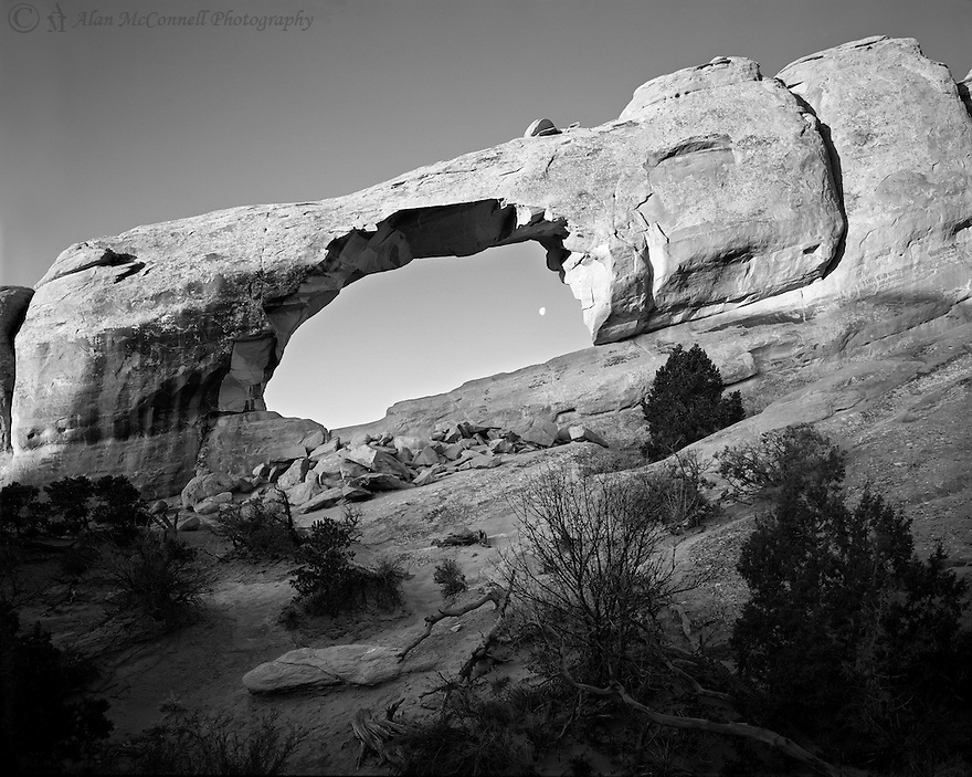 """""""Skyline Arch and the Moon""""<br /> Arches National Park, Utah<br />  2012<br /> <br /> The morning sun strikes Skyline Arch as the setting moon peeks through the gap.  This beautiful arch can be found right beside the Devils Garden Campground and is easily accessible.  During the day, many kids discover a great place to hike around the slick rock while their parents prepare a meal.<br />   <br /> 4 x 5 Large Format Film"""