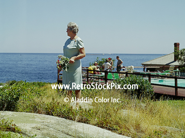 Ralph Waldo Emerson Hotel, Rockport, Maine. Woman with flowers looking out to sea. 1959
