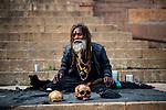 An Aghori Sadhu (holy man) with his human skull at a ghat in Varanasi, Uttar Pradesh, India.