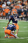 Syracuse Orange kicker Ryan Norton (12) attempts a kick as Charley Loeb (17) holds during a game against the Boston College Eagles at the Carrier Dome on November 30, 2013 in Syracuse, New York.  Syracuse defeated Boston College 34-31.  (Copyright Mike Janes Photography)