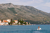 A man standing in a small boat with a Honda outboard motor on the blue sea, in the background the massive mountains of the Peljesac peninsula and the village Mount Sveti Ilija mountain. Orebic town, holiday resort on the south coast of the Peljesac peninsula. Orebic town. Peljesac peninsula. Dalmatian Coast, Croatia, Europe.
