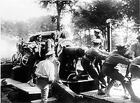 With the Canadians in the great battle<br /> Description<br /> <br /> Ramming home a huge shell in a heavy howitzer