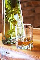 Rakija grappa type spirit flavoured with herbs backlit, Travarica, Toreta Vinarija. Detail with glass and herbs in bottle Toreta Vinarija Winery in Smokvica village on Korcula island. Vinarija Toreta Winery, Smokvica town. Peljesac peninsula. Dalmatian Coast, Croatia, Europe.