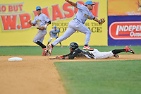 Tony Thomas (2) of the New Britain Rock Cats slides head first into second base under shortstop KC Serna during a game against the Reading Fightin Phils at New Britain Stadium on July 13, 2014 in New Britain, Connecticut.  (Gregory Vasil/Four Seam Images)