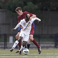 Boston College midfielder Derrick Boateng (10) as Harvard University midfielder Kevin Harrington (21) closely defends.Boston College (white) defeated Harvard University (crimson), 3-2, at Newton Campus Field, on October 22, 2013.