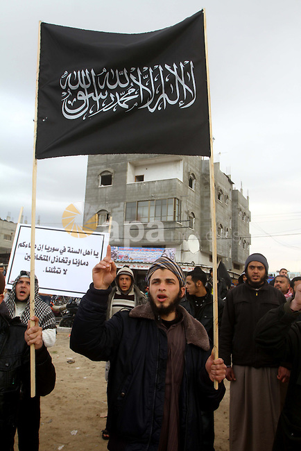 """Palestinian Salafists take part in a protest against Syria's President Bashar al-Assad in Rafah in the southern Gaza Strip February 24, 2012. The black flag reads """"There is no god but Allah and Mohammad is the prophet"""". The white sign reads """"Where are the traitor Arab rulers"""". Photo by Ashraf Amra"""
