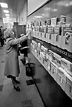 Post Office 1980s London UK. People filling in forms selecting leaflets. 1981