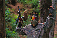 Woman holding both hands up in surrender while engaged in paintball sport, a paramilitary leisure type game
