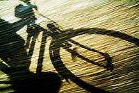 Shadow of a person riding a bicycle.