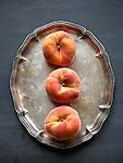 Three whole fresh peaches on a silver platter.