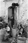 Oaxaca, Mexico 1970s Indigenous Mexican native indian women sit below a hand crafted Bull firework above the doorway. They are selling produce outside the covered market building. 1973