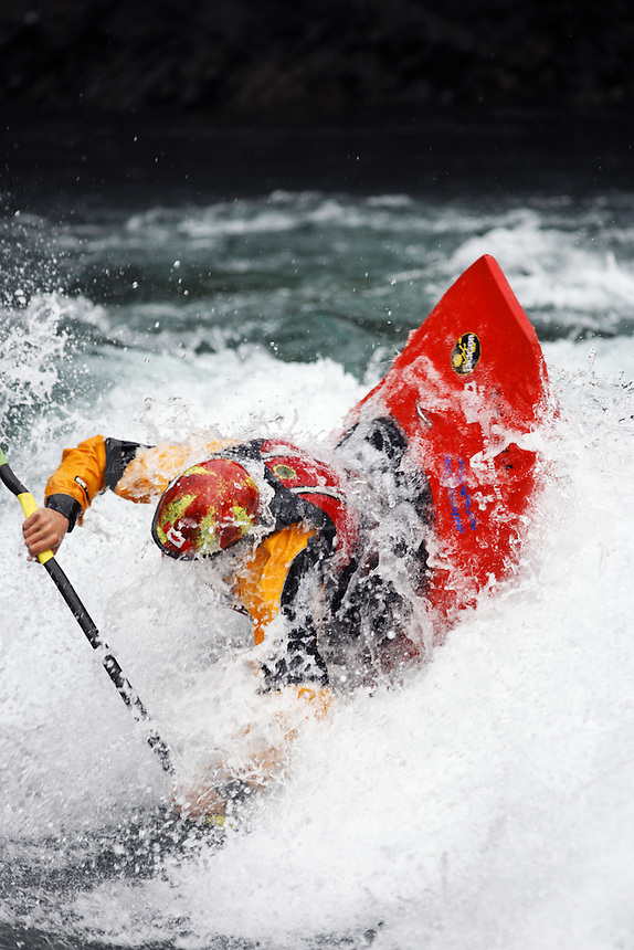 Andrew Jobe dives into a hole in a whitewater kayak on the Kananaskis River, Kananaskis County, Alberta, Canada