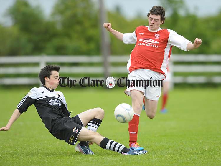 Michael Davenport of Moher Celtic in action against Ian Collins of Newmarket Celtic during their U-19 final at The County Grounds, Doora. Photograph by John Kelly.
