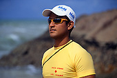 Costa do Sauipe, Bahia, Brazil. Cool lifeguard in yellow t-shirt and sunglasses and white baseball cap.