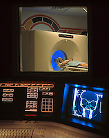 A view of the control room in a hospital as a patient recieves a CAT scan. A monitor displays a computerized image of a skull.