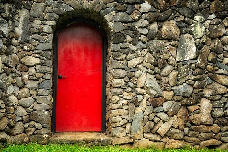 Red door in rock wall. Maui, Hawaii