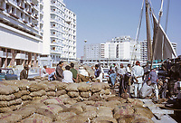 Dubai 1972, United Arab Emirates.  Unloading Cargo from a Dhow alongside the Creek.  Office and Apartment Buildings in the background.
