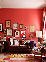 Cushions of differing sizes adorn a brown velvet two-seater sofa in the living room, the red wall decorated with a collection of framed drawings and paintings