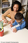 Education Preschool 3-5 year olds boy drawing with marker working on writing the letters of his name female teacher working with him vertical