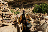 MALI Dogon Land , Dogon village with clay architecture at the Falaise which is UNESCO world heritage, dogon man  / MALI, etwa 20 km südoestlich von Bandiagara verlaeuft die rund 200 km lange  Falaise , UNESCO Welterbe, eine teilweise stark erodierte Sandsteinwand bis zu 300 m Hoehe  , hier befinden sich viele Dogon Doerfer in Lehmbau Architektur