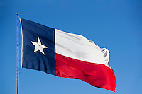This is the State of Texas Flag flying in the wind. it is on a flagpole against a blue sky.