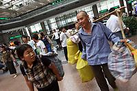 CHINA. Beijing. People carrying their belongings in Beijing West Train Station. 2007.