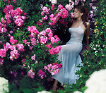 Romantic sensual portrait of a beautiful woman in a long elegant summer dress sitting on the stairs in a garden smelling the pink rose flowers Image © MaximImages, License at https://www.maximimages.com